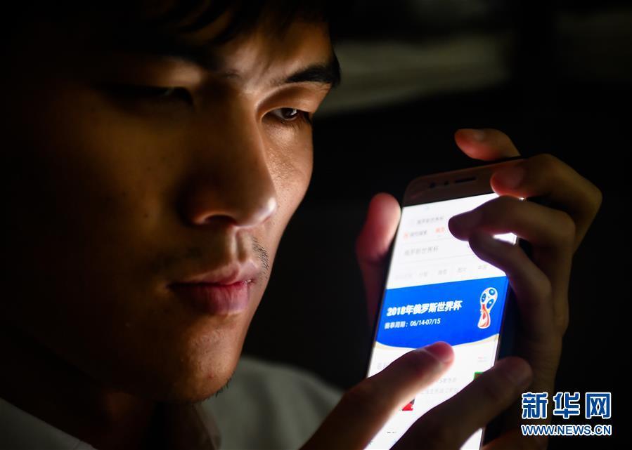 孙东远在寝室通过手机收听世界杯赛程信息(6月20日摄)。新华社记者 许畅 摄